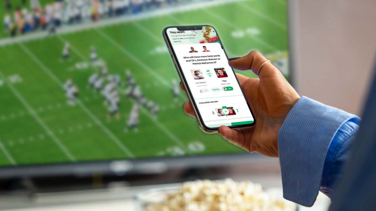 A person uses the FanUp app while watching the game.